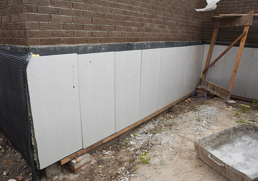 foam boards are installed before applying waterproofing membrane to insulate the exterior foundation wall